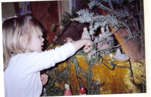 Anika placing the baby Jesus figurine in a family nativity scene called a creche.