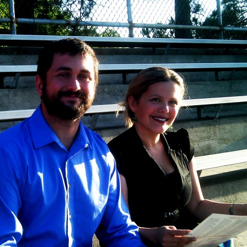Mr. and Mrs. Kevin Joseph Granger arrived early after preparing the reception and were waiting in the bleachers for the ceremony to begin on a beautiful evening.