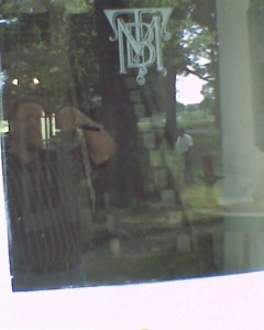 A dim reflection of myself taking a photograph of the door of Kisinoaks on a family unpaid work day.
